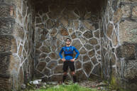 Portrait of trail runner standing at a wall - RAEF02296