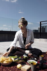 Stylish woman with sunglasses having a healthy meal on the roof - EYAF00455