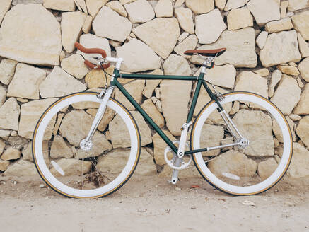 Fixie bike leaning against natural stone wall - DLTSF00045