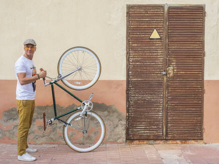 Man with Fixie bike standing in front of a wall - DLTSF00048