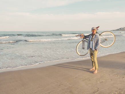 Barefoot man standing with Fixie bike on his shoulder on the beach - DLTS00054