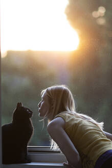 Black cat and woman in front of window at sunset - CHPF00569