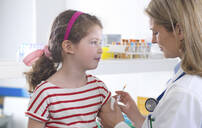 Female doctor giving a young girl a routine vaccination in the clinic - ABRF00619