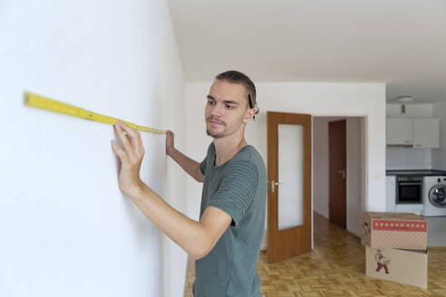 Young man measuring the wall in an empty apartment - FLLF00283