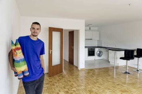 Young man standing in an empty apartment holding a pinata - FLLF00286