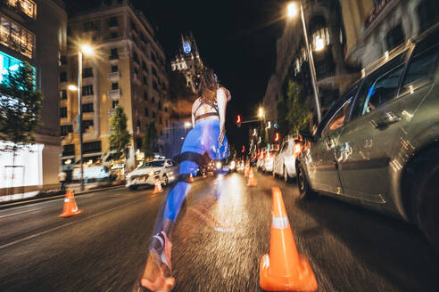 Woman running in Madrid city with flashing lights at night - JCMF00157