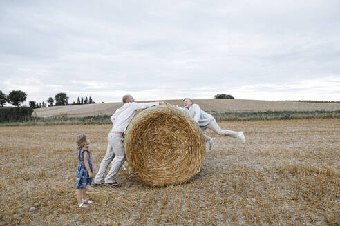 Father and his children playing on hay bales - KMKF01074