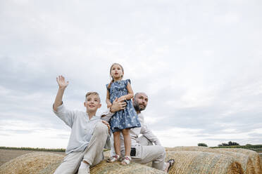 Father and his children sitting on hay bales, watching sky - KMKF01080