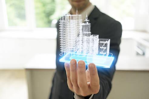 Businessman holding hologram of architectural model - KSHSF00012