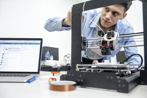 Student setting up 3D printer, using laptop - VPIF01475