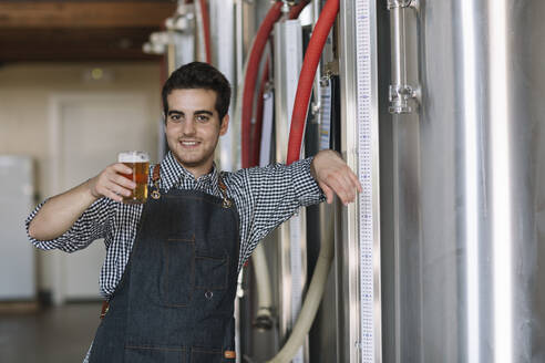 Portrait of confident young man holding beer glass at a brewery - ALBF01077