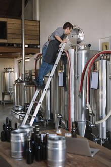 Young entrepreneur working at tank at a brewery - ALBF01086