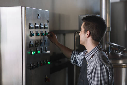 Young entrepreneur working at a brewery turning on switch - ALBF01095