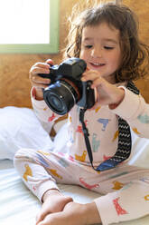 Cute little girl in pajamas in bed with a camera - GEMF03123