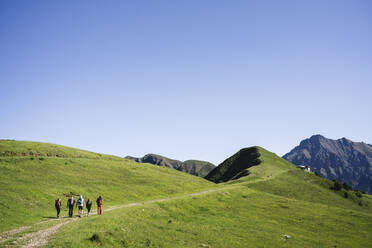 Group of hikers walking in the mountains, Orobie Mountains, Lecco, Italy - MCVF00003