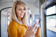 Smiling young woman using smartphone in a tram - BSZF01332