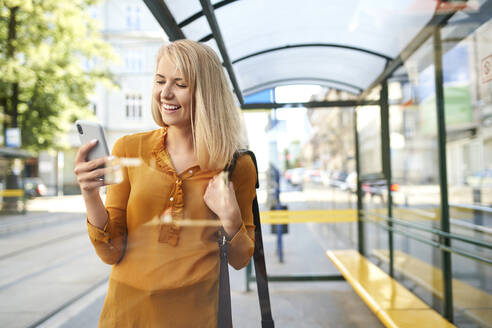 Smiling young woman using smartphone at tram stop - BSZF01335