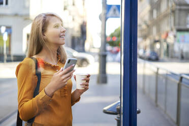 Smiling young woman with smartphone and takeaway coffee checking the schedule at bus stop - BSZF01341