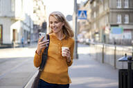 Smiling young woman with smartphone and takeaway coffee in the city - BSZF01344