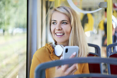 Smiling young woman with smartphone in a tram - BSZF01347