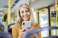 Smiling young woman using smartphone in a tram - BSZF01350