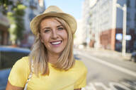 Portrait of happy young woman in the city - BSZF01356