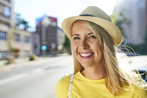 Portrait of happy young woman in the city - BSZF01359