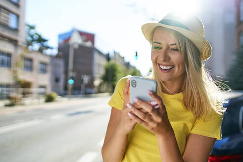 Happy young woman using smartphone in the city - BSZF01362