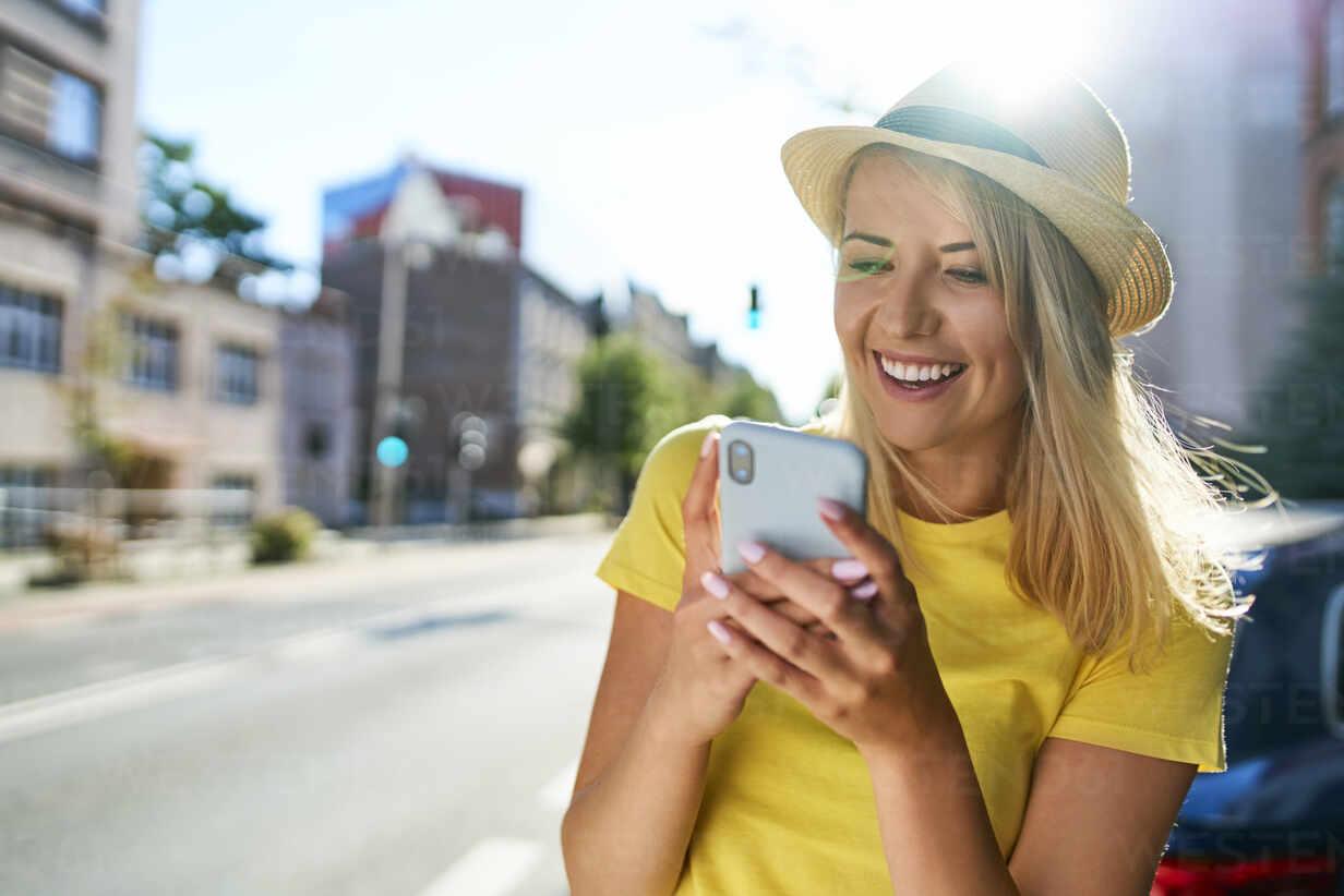 Happy young woman using smartphone in the city - BSZF01362 - Bartek Szewczyk/Westend61