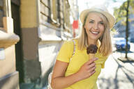 Portrait of smiling young woman enjoying an ice cream in the city - BSZF01365