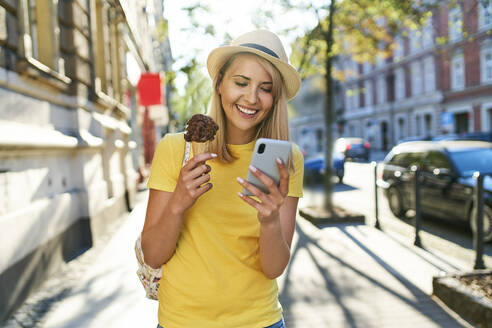 Smiling young woman with ice cream and cell phone in the city - BSZF01368