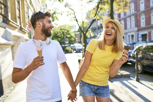 Happy young couple enjoying ice cream in the city - BSZF01371