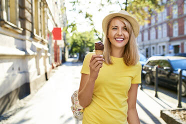 Smiling young woman enjoying an ice cream in the city - BSZF01374