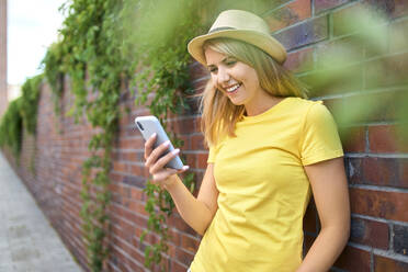 Happy young woman standing at a brick wall using smartphone - BSZF01377