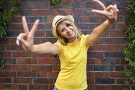 Portrait of happy young woman standing at a brick wall making peace sign - BSZF01380