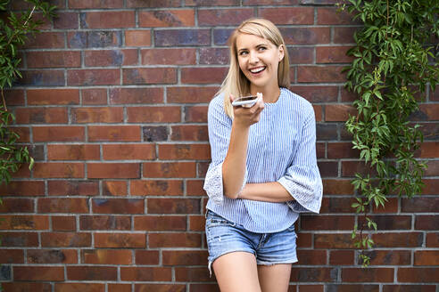 Happy young woman standing at a brick wall using smartphone - BSZF01386