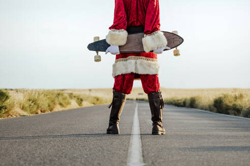 Low section of Santa Claus holding a longboard on country road - JCMF00173