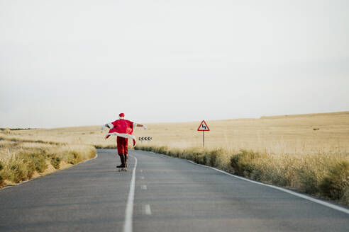 Santa Claus riding on longboard on country road - JCMF00176