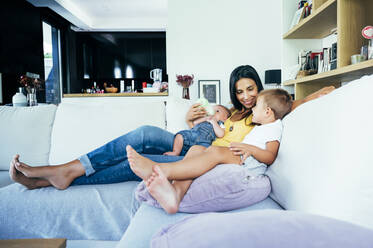 Mom with her two sons sitting on a sofa - OCMF00617