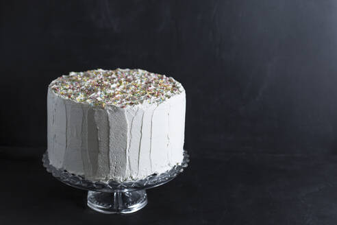 Close-up of cream cake against wall in studio - STBF00358