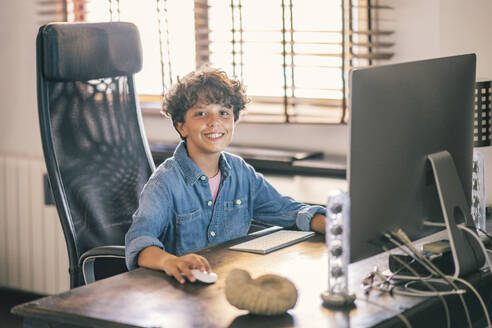 Portrait of smiling boy sitting at desk at home using personal computer - DLTSF00064