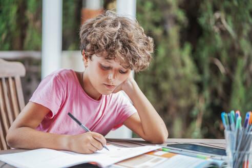 Boy sitting at garden table doing homework - DLTSF00079