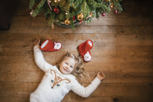 Smiling girl lying under the Christmas tree - IPF00528