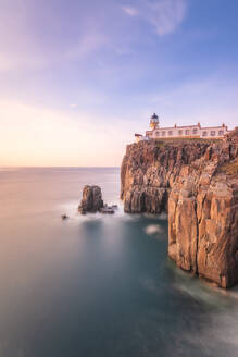 Neist Point Lighthouse by sea against sky during sunset at Waterstein, Isle of Skye, Highlands, Scotland, UK - SMAF01491