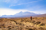 Mature woman standing on land while Cuillin mountains in background, Isle of Skye, Highlands, Scotland, UK - SMAF01503