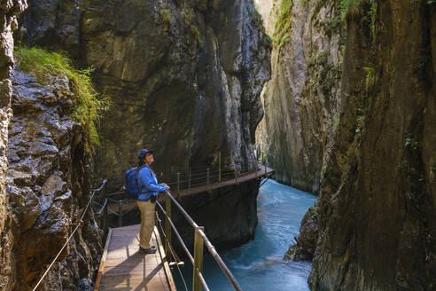 Side view of senior woman standing on footbridge at Wasserfallsteig in Leutasch Gorge, Tyrol, Austria - SIEF09006