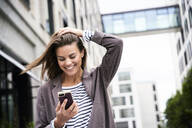 Happy businesswoman using smartphonein the city - PNEF01852