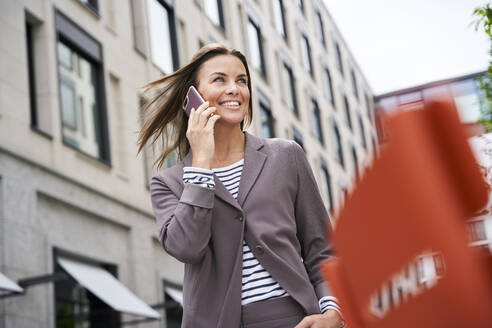 Happy businesswoman on the phone in the city - PNEF01855