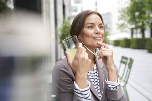 Businesswoman with earphones listening to music at an outdoors cafe - PNEF01861