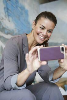 Happy businesswoman using smartphone - PNEF01879